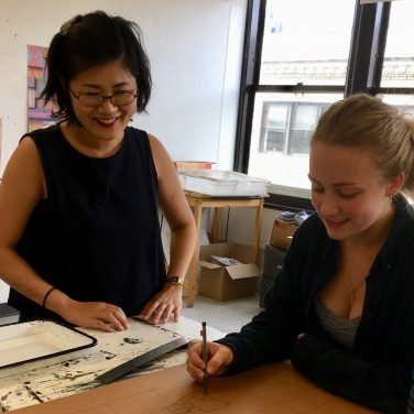 Aki Ingrid working with a student