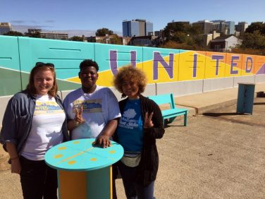 West Side Grows Together's Sarah Lester, volunteer Brenden Cephas and United Neighbors organizer Vanity Constance stand in front of a mural on the Seventh Street bridge over I-95