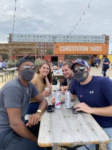 three guys and a girl drinking white claw at consitution yards in masks